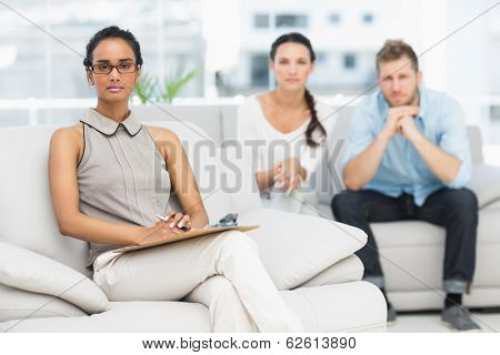 Portrait of therapist and unhappy couple in therapists office
