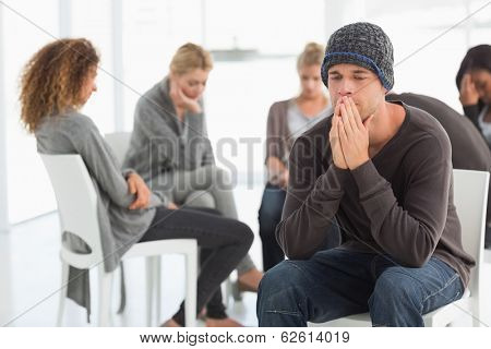 Upset man at rehab group with hands to face at therapy session