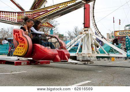 Teens Enjoy Fast Moving Carnival Ride At Fair