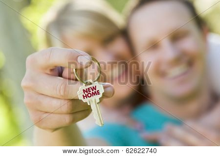 Happy Couple Holding House Key with New Home Text On The Key.