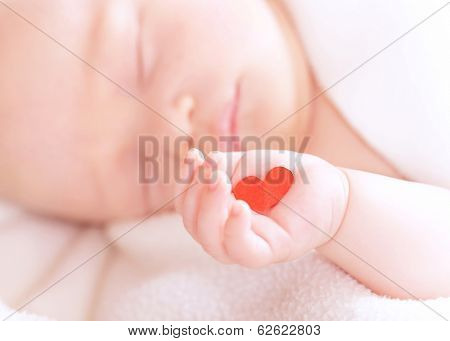 Closeup portrait of cute newborn baby sleeping, holding in hand little red heart, innocent child, soft focus, hope and help concept
