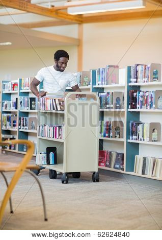 Young male librarian with trolley books in library