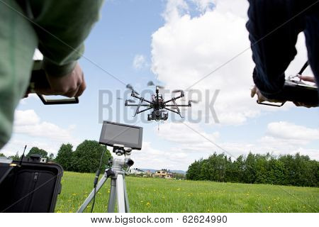 Octocopter being operated by a photographer and pilot in open green park