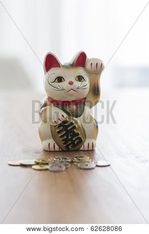 A beckoning cat and coin