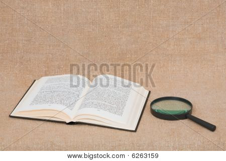 Composition From Opened Book And Magnifier Lying On Canvas