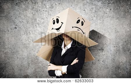 Businesswoman wearing carton box with drawn smiley on head