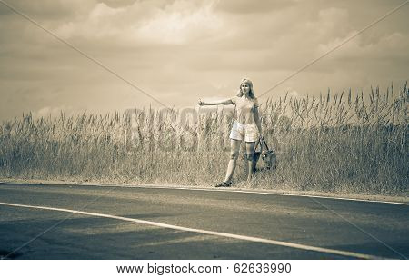 Hitchhiking girl votes on roadwith a retro effect