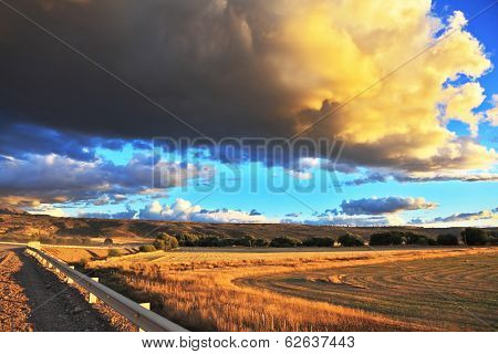 The enormous storm cloud and a flat plain covered in orange sunset.  In the steppe runs a gravel road. Storm over the Pampas