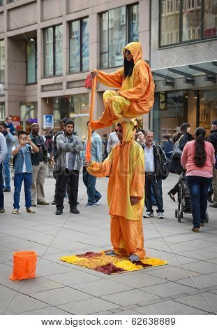 STUTTGART, GERMANY - APRIL 01, 2014: Street actors shows magic trick