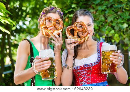 In Beer garden - female friends in Tracht, and Dirndl drinking a fresh beer and eating pretzel in Bavaria, Germany