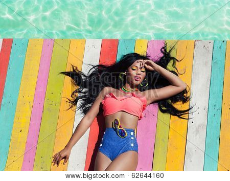 Tropical summer holiday fashion vogue concept - african american woman on a wooden pier background