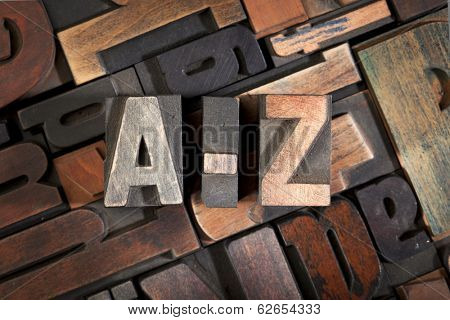 a-z written with vintage letterpress printing blocks on random letters background