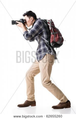 Asian young male backpacker take a picture, full length portrait isolated on white.