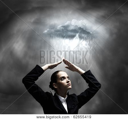 Young crying businesswoman with arms covering head from rain