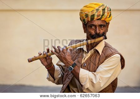 JODHPUR, INDIA - NOVEMBER 26, 2012: Indian man plays wooden flute in Mehrangarh fort, Rajashtan, India