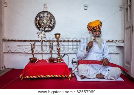 JODHPUR, INDIA - NOVEMBER 26, 2012: Old Indian man smokes hookah (waterpipe) in Mehrangarh fort. The concept of hookah is thought to have originated In India