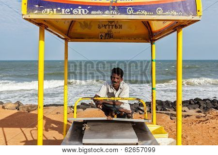 PONDICHERRY, INDIA - FEBRUARY 2, 2013: Unidentified Indian street ice cream vendor with cart on beach
