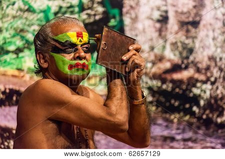 KOCHI, INDIA - FEBRUARY 24, 2013: Unidentified Kathakali exponent preparing for performance by applying face make-up. Kathakali is the classical dance form of Kerala