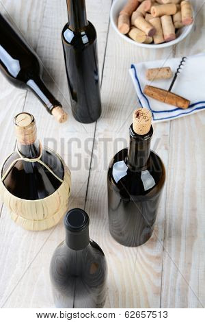 Wine still life shot from a high angle. Five bottles of wine with a cork screw napkin and bowl of corks on a rustic farmhouse style table. Vertical format.