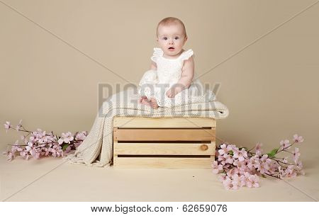 Baby Girl With Cherry Blossom Flowers In Spring Dress On Blanket