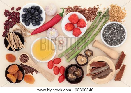 Super food selection forming an abstract background of handmade mottled paper..