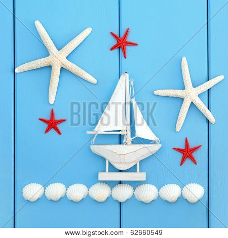 Seaside background abstract with starfish, cockle shells and boat decoration over blue wood.