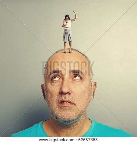 displeased screaming woman and tired senior man over grey background