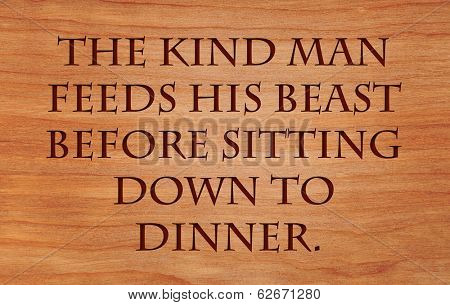 The kind man feeds his beast before sitting down to dinner - Hebrew Proverb on wooden red oak background