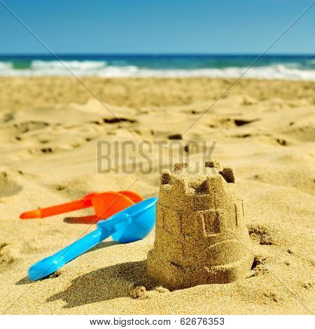 a sandcastle and toy shovels on the sand of a beach, with a retro effect