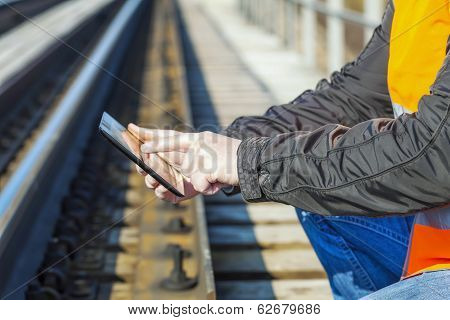 Railroad worker with tablet PC near railway