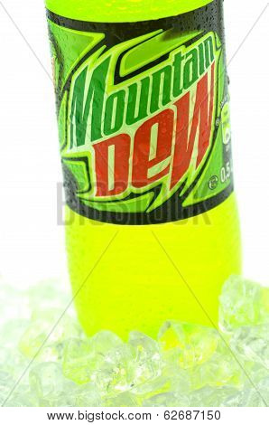 Bottle of Mountain Dew drink on ice isolated on white