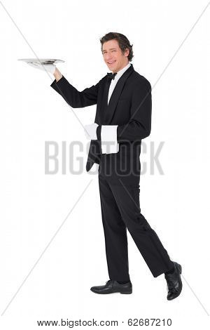 Full length portrait of server carrying tray isolated over white background