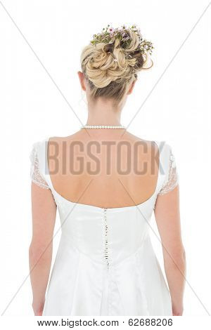 Rear view of bride wearing flowers in hair over white background