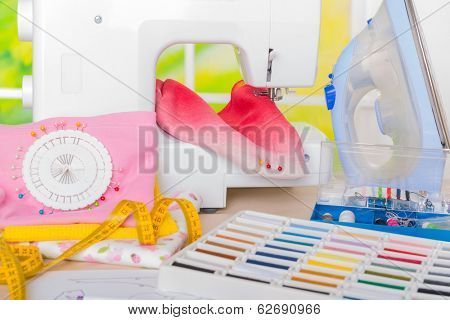 Sewing machine with colorful fabrics, threads and other sewing accesories.