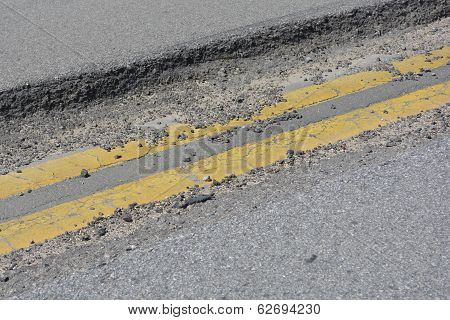 Old asphalt with two yellow bands