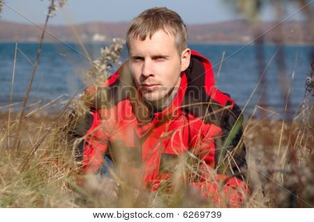 Young Blond Man In Red Jacket Sit On The Seashore.