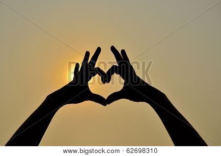 Hands Together As A Heart Shape In Silouette With Sun In Background