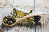 stock photo of kalamata olives  - A glass bottle of olive oil and a wooden spoon with olives on a table - JPG