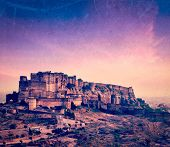 Vintage retro hipster style travel image of Mehrangarh Fort in twilight on sunset, Jodhpur, Rajastha
