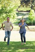 Full length of excited couple running in park