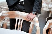 Close up of groom in black suit with hand on restaurant chair