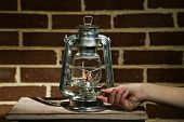 pic of kerosene lamp  - Hand lights a kerosene lamp on brick wall background - JPG