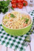 Tasty instant noodles with vegetables in bowl on table close-up