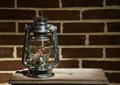 stock photo of kerosene lamp  - Burning kerosene lamp on brick wall background - JPG