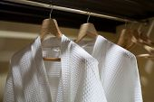 foto of housecoat  - Close up white robes with wooden hangers