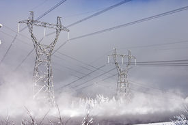 pic of power lines  - Powerful power station costing in an environment of snowdrifts on a background of the blue sky - JPG