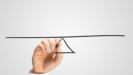 picture of seesaw  - Man drawing a seesaw to demonstrate the concept of a lever and fulcrum of balance equilibrium and equality on a grey background with copyspace - JPG