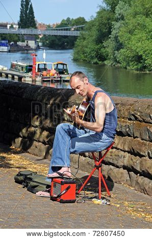Guitarist busking on riverbank, Chester.