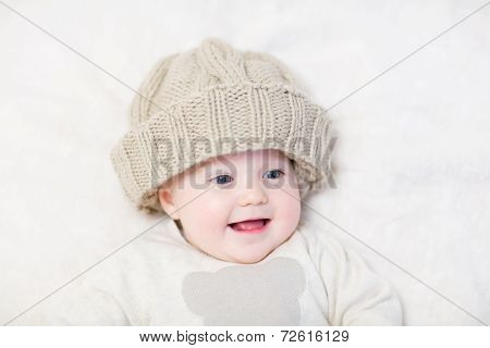Funny laughing little baby in big knitted hat and warm sweater