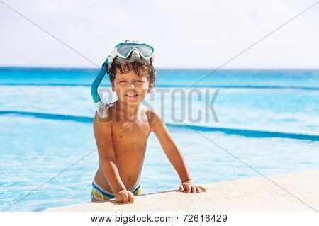 Happy smiling boy with snorkel mask on his head
